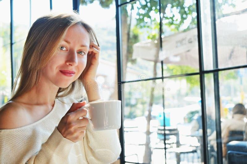 Photo sensuelle de la jeune belle femme jouant de la musique dans la lumi?re naturelle du soleil des fen?tres int?grales du caf? photo stock
