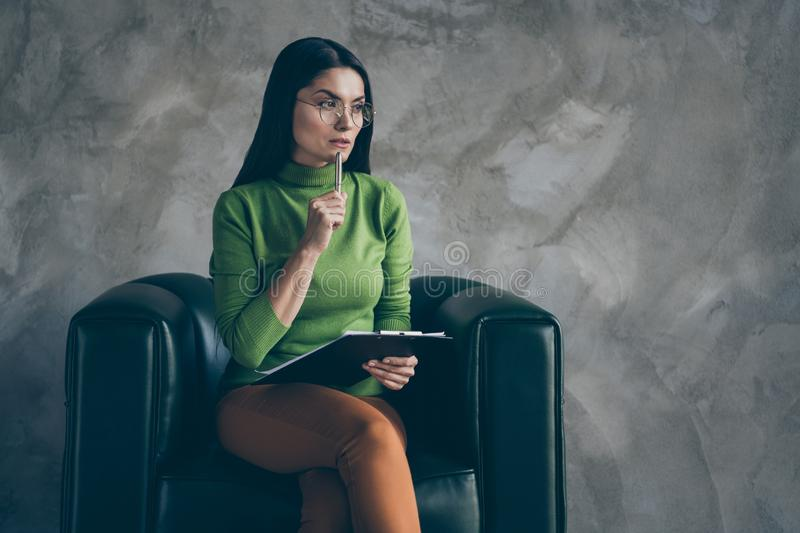Photo of serious confident woman in orange pants touching chin with pen holding clipboard looking into empty space royalty free stock photos