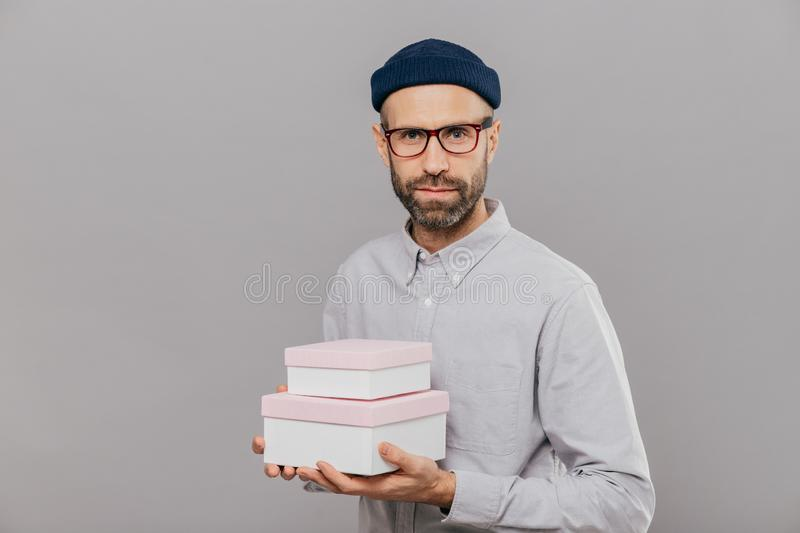 Photo of serious male model dressed in festive clothes, holds gifts in hands, going to congratulate friend with birthday, ready stock image