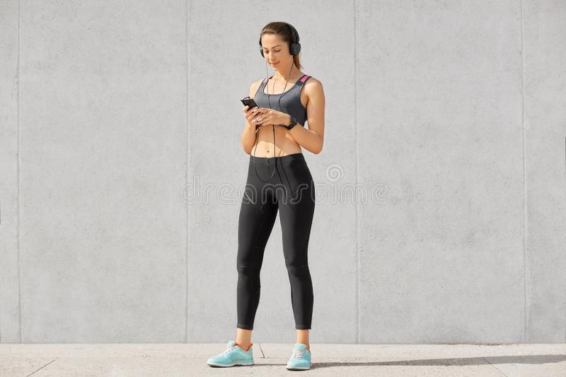 Photo of serious sporty atheltic woman holds modern cell phone, listens music with headphones, wears smartwatch, chooses her favou. Rite track, dressed in stock photography
