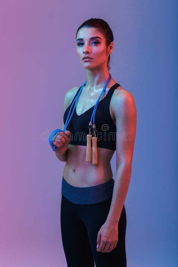 Serious strong young sports woman holding skipping rope. Photo of serious strong young sports woman standing isolated over purple wall background. Looking royalty free stock photo