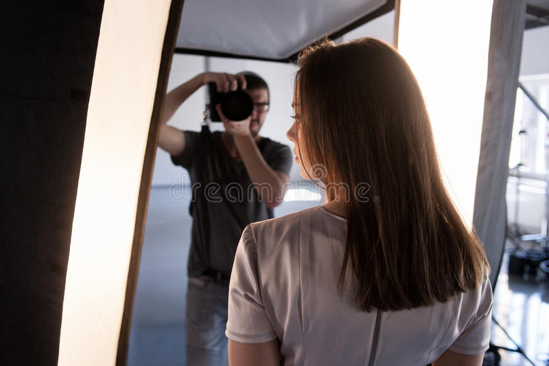 Photo session backstage. Photographer shoot model. Back view from woman`s shoulder on studio interior and man, who work with camera royalty free stock photo