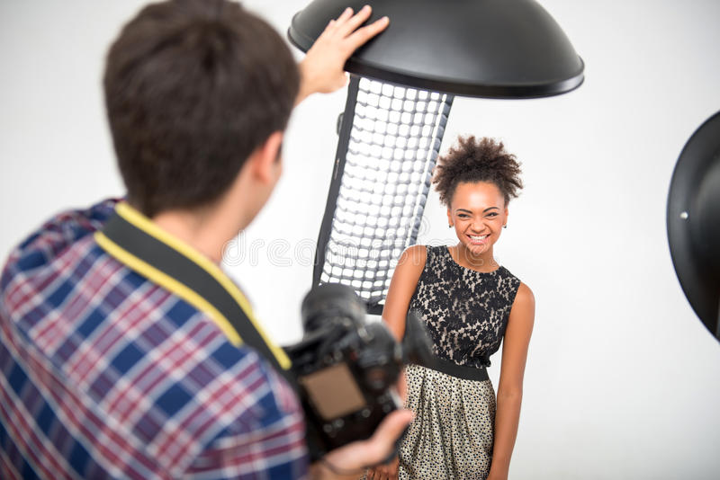 Photo session of the great model. Selective focus on the lovely smiling African model wearing wonderful evening dress standing in front of projectors looking at royalty free stock images