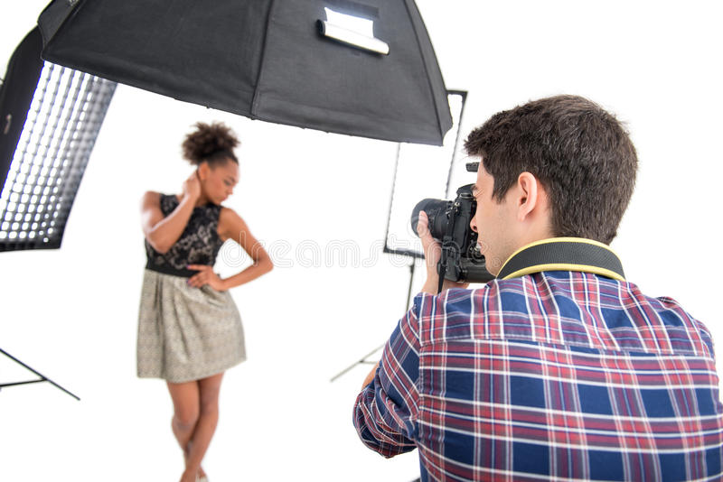Photo session of the great model. Selective focus on the photographer wearing nice checked shirt standing back to us animated his work photographing the model on royalty free stock image