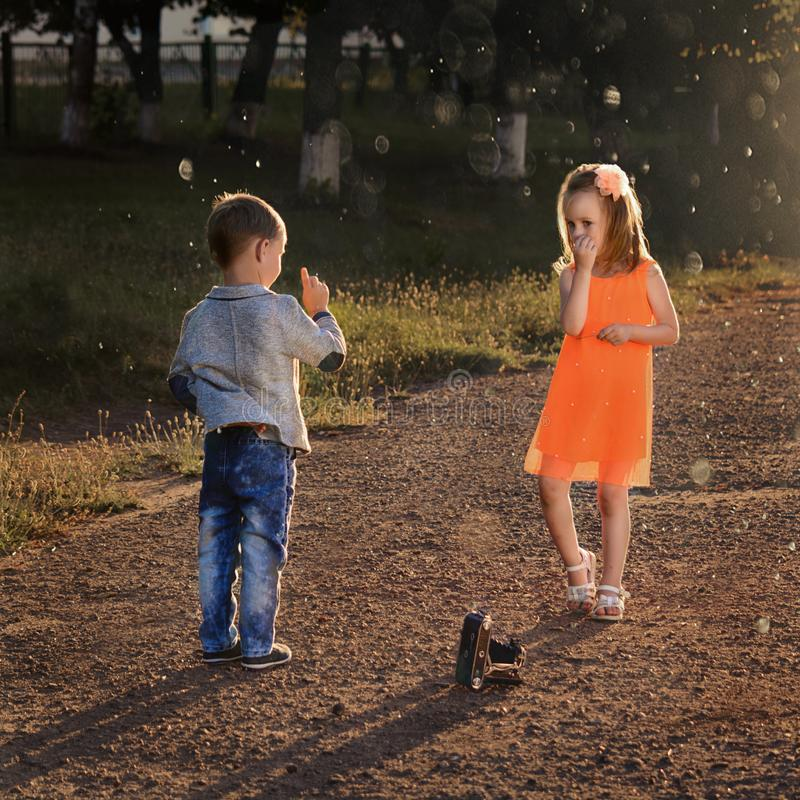 Photo session of a little photographer. NnPhoto session of a little boy and girl with an old photo camera at sunset royalty free stock images