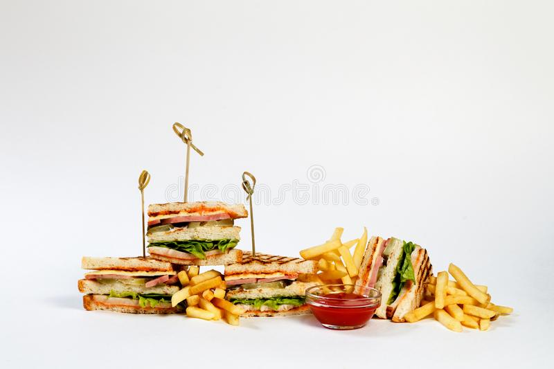Photo session new menu of coffee house, fresh club sandwich with chicken and vegetables, lettuce salad, french fries, ketchup royalty free stock photo