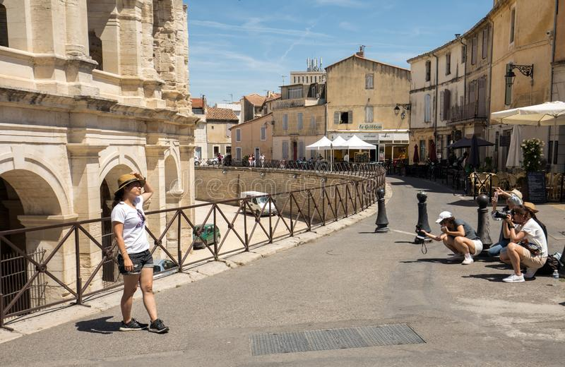 Photo session of tourists from Asia in front of the ruins of the Roman Arena in Arles stock photo
