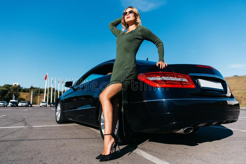 Photo of blonde woman in sunglasses in long dress standing near black car with open door royalty free stock image