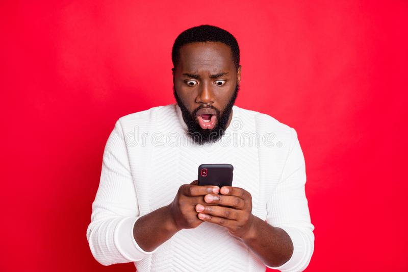 Photo of shocked dark skin man holding telephone hands reading bad blog comments open mouth wear white knitted sweater. Isolated red background royalty free stock photography