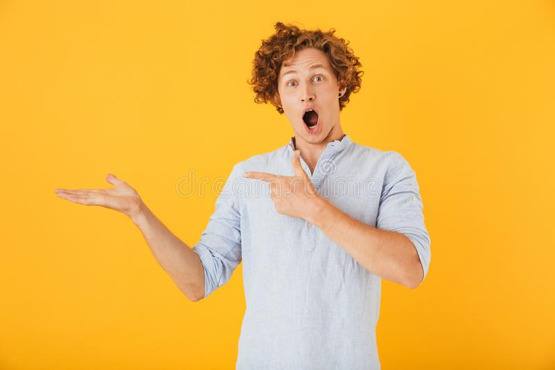 Photo of shocked european man 20s shouting and holding copyspace at palm, isolated over yellow background. Photo of shocked european man 20s shouting and holding stock photo