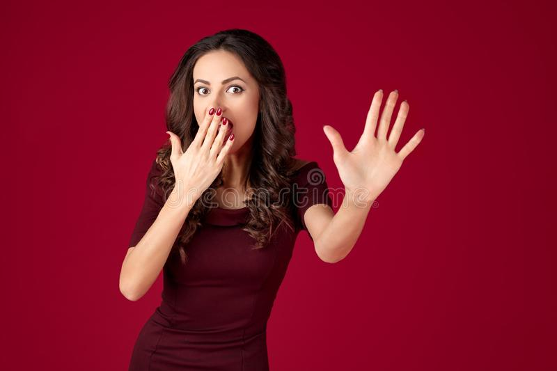 Photo of shocked young woman in maroon dress show stop gesture over red background. Photo of shocked young woman in maroon dress show stop gesture over red stock photography
