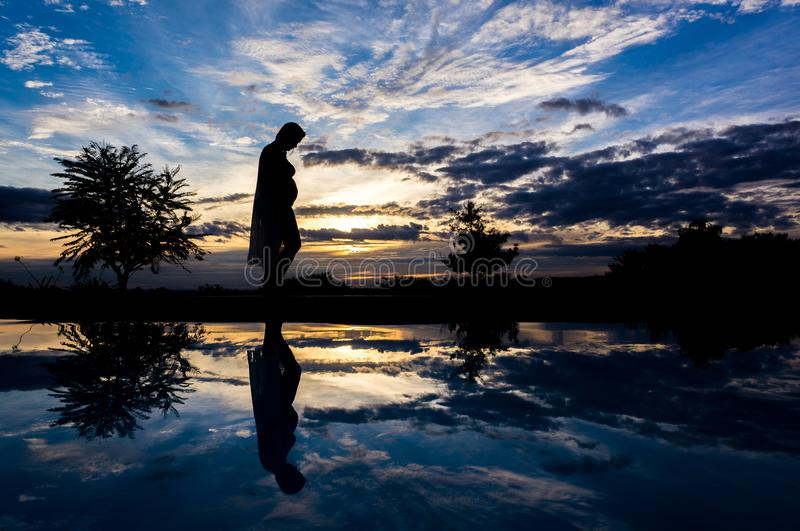 Pregnant woman standing at sunset royalty free stock images