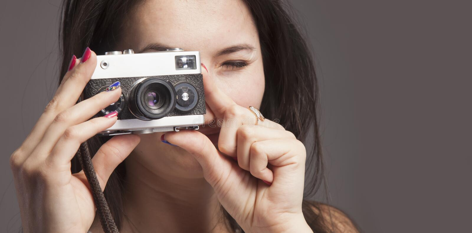 Photo shooting. Close up young beautiful female photographer taking pictures with vintage retro camera stock photo