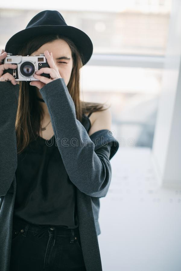 Photo shooting. Stylish beautiful girl holding the retro style cam. Catch the moment stock photos
