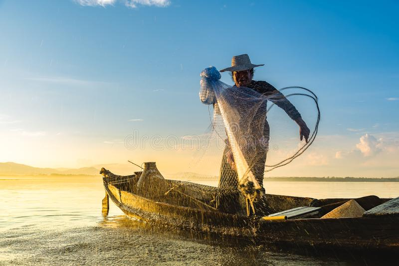 Photo shot of water spatter from fisherman while throwing fishing net on the lake. Silhouette of fisherman with fishing net in mo stock image