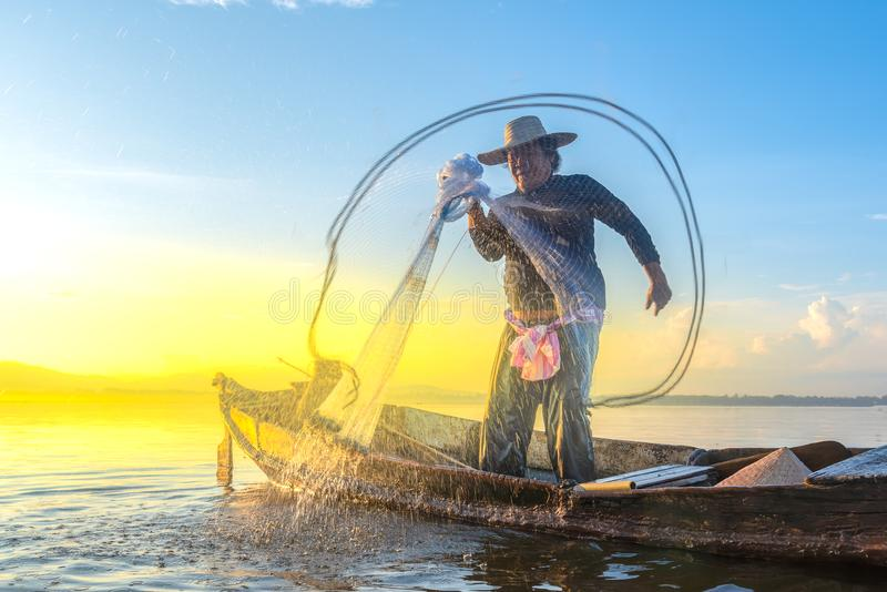Photo shot of water spatter from fisherman while throwing fishing net on the lake. Silhouette of fisherman with fishing net in mo stock photography