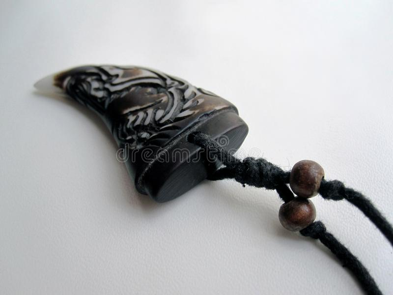 Dragon tooth amulet. This photo shows the amulet on which the dragon pattern is carved royalty free stock photography