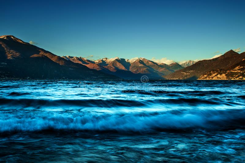 Agitated lake in sunny day. The photo shows a landscape from Bellagio, on lake of Como, in a windy day, with the agitated lake, and the snow on the peaks of the stock image