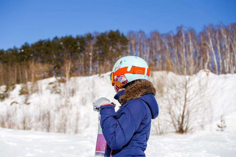 Photo of side view of sporty woman in helmet with snowboard looking at camera. In winter day stock photos