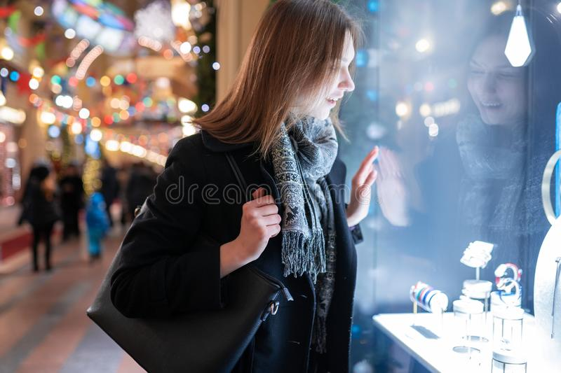 Photo side of young woman at shop window in evening. At winter royalty free stock photo
