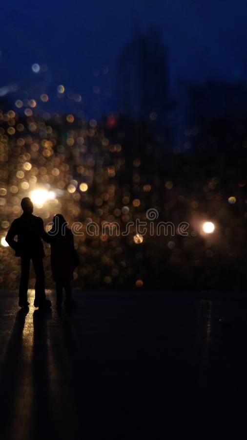 Silhouette of Mini Figure Romantic Couple Enjoy Light Lamp in the rainy evening stock photography