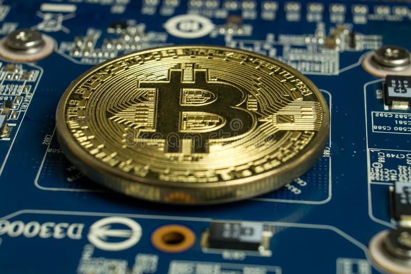 A single Bitcoin coin on the blue computer motherboard stock photo