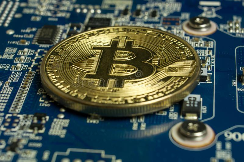A single Bitcoin coin on the blue computer motherboard royalty free stock photo