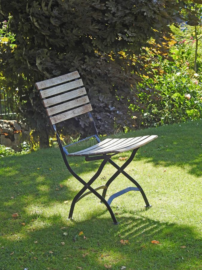 Single chair garden seat bench on grass lawn summer shade. Photo of a single wooden garden chair seat on grass lawn with filtered summer sun through trees in royalty free stock images