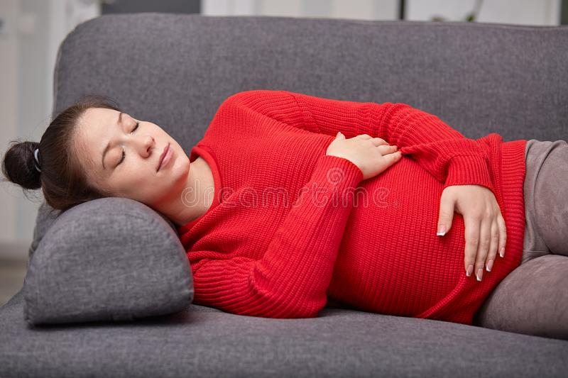 Photo of sleepy tired pregnant woman takes nap, keeps hands on belly, wears red warm sweater, enjoys good rest on sofa at home, stock images
