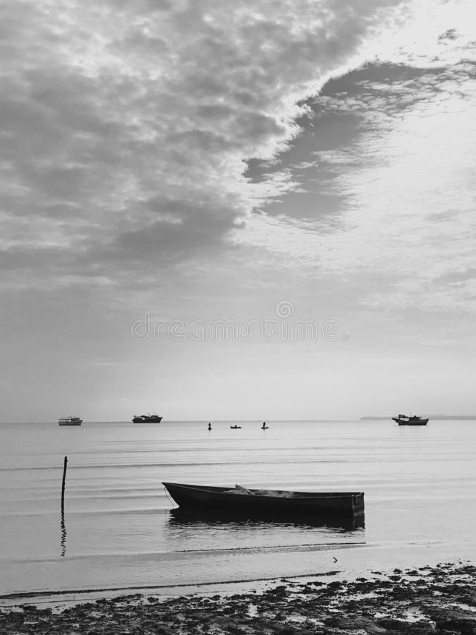 Photo of small fisherman boat moored near the shore in the samana bay. Picture of small fisherman boat silhouette moored near the beach of atlantic ocean. Sky is royalty free stock photo