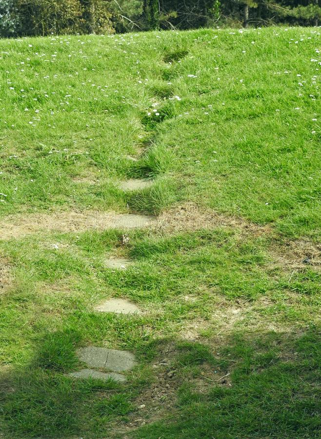 Tranquility grass path stepping stones lawn hill stock photo