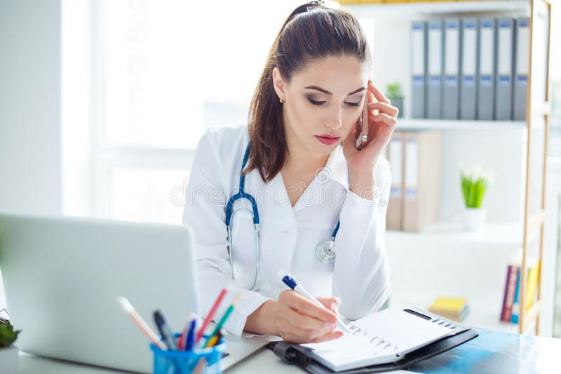 Photo of smart young confident female doctor sitting at the table receiving a call from a patient and writing information in note royalty free stock images