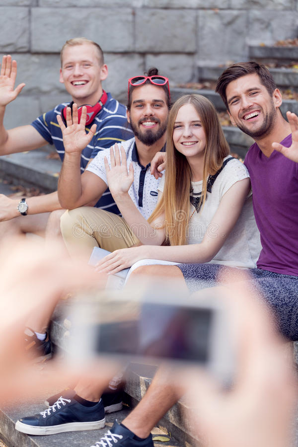 Photo by smartphone. Group of happy friends having photo done by smartphone royalty free stock image