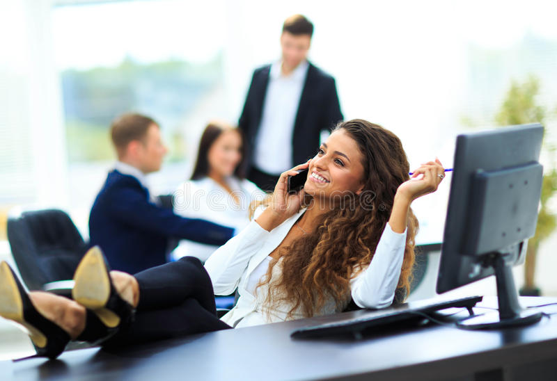 Photo of smiling brunette businesswoman. With legs on the desk phoning in office royalty free stock images