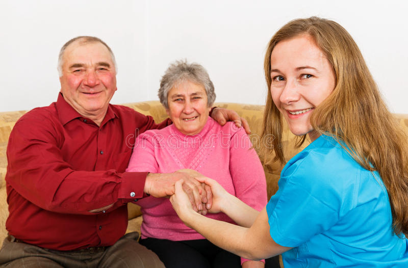 Smiling elderly couple and young caregiver royalty free stock photography