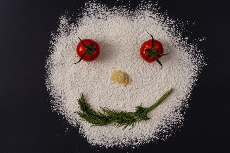 Photo of smiling faces from tomato parsley flour lying on a black stock photo