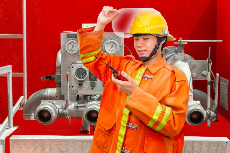 Photo of smiling firefighter wearing helmet and using walkie talkie near fire truck with fire hose. stock image