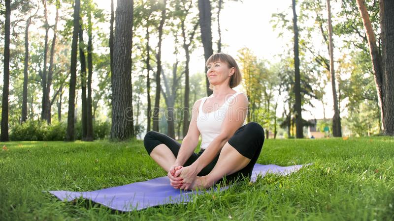 Photo of smiling happy woman 40 years old doing yoga exercises on fitness mat at forest. Harmony of human in nature royalty free stock photos