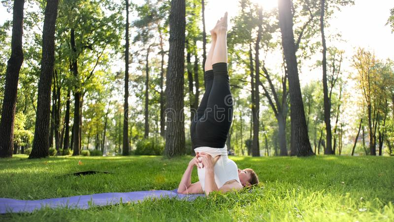 Image of smiling middle aged woman in fitness clothes doing stretching and yoga exercises. WOman meditating and doings stock photo