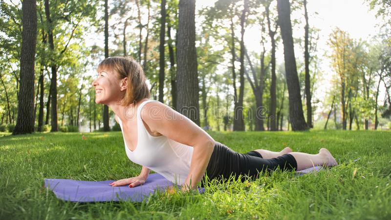 Image of smiling middle aged woman in fitness clothes doing stretching and yoga exercises. WOman meditating and doings royalty free stock photography
