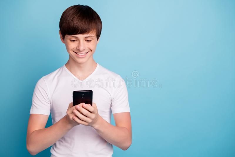Photo of smiling rejoicing boy having received message from his classmate girl he has liked since they went to. Photo of smiling rejoicing boy, having received royalty free stock images