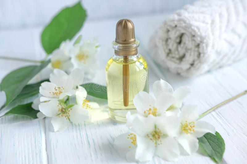 Photo for a spa center with a jar of jasmine oil and jasmine flowers. Aromatherapy and oil for massage. Cosmetic oil jasimna. Photo for a spa center with a jar royalty free stock image