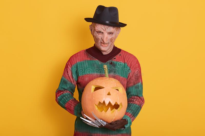 Photo of spooky man on halloween party, wearing stripes old sweater and black hat, creepy guy holding carved pumpkin isolated over stock photography