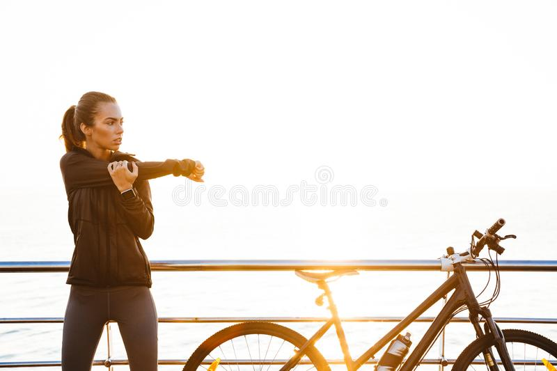 Photo of sporty woman doing stretching exercises, while standing near bicycle outdoors during sunrise over ocean stock images