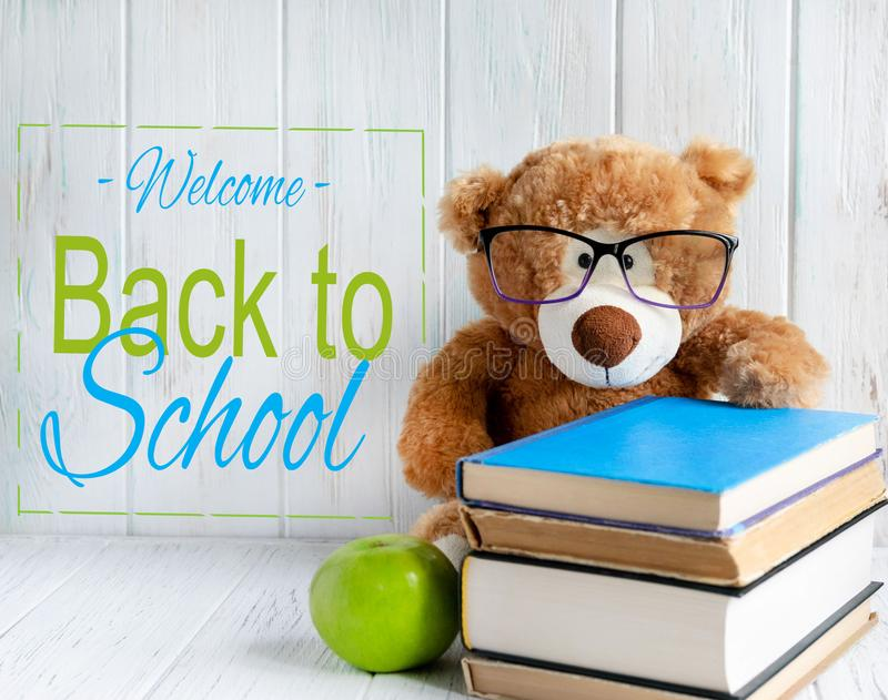 Photo of a stack of books with a bear, an apple and a place for an inscription on a wooden background. Back to school concept. royalty free stock images