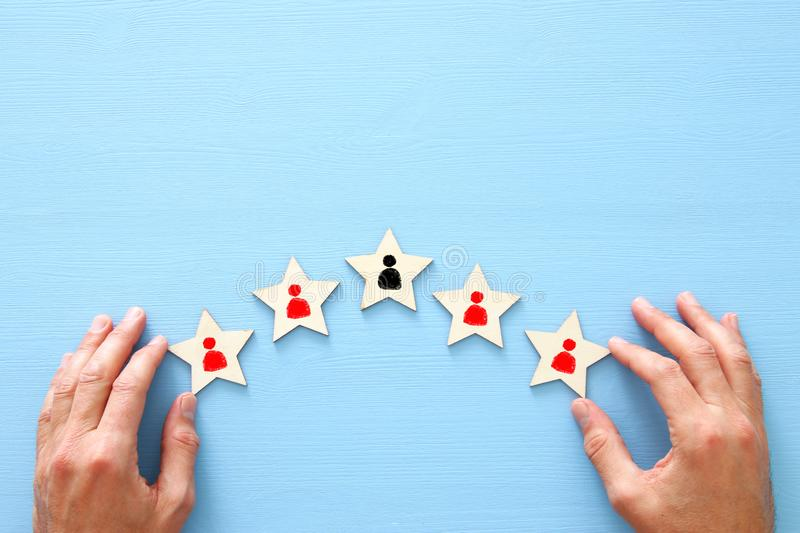 photo of 5 star symbols with people icons over wooden table ,human resources and management concept. royalty free stock image
