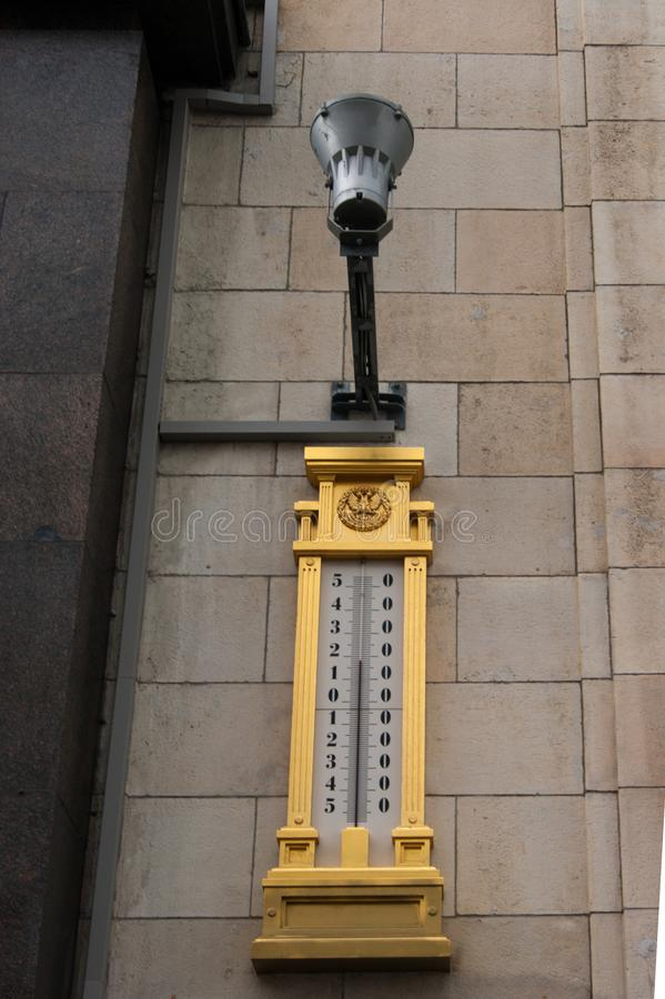 Photo of street design. An electric lamp on one of the buildings above a gilded street thermometer showing the temperature of the royalty free stock photography