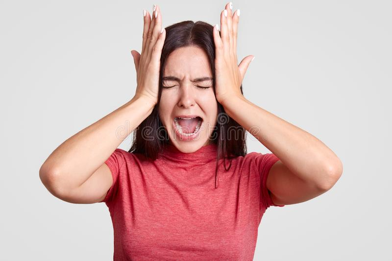 Photo of stressful brunette female has terrible headache, being in panic as lost her close person, feels desperate, isolated over royalty free stock image