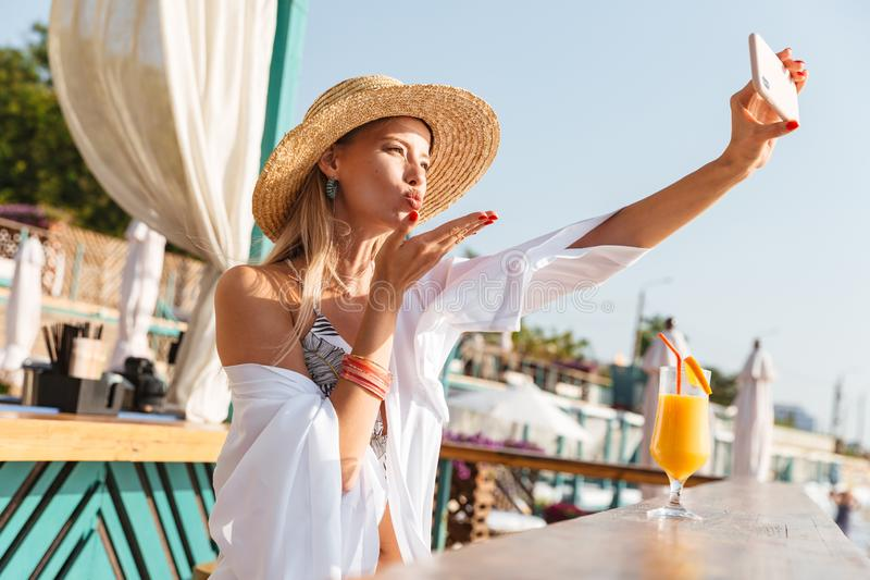 Photo of stunning blond woman 20s in straw hat smiling and taking selfie on mobile phone, while drinking orange juice in beach ba. Photo of stunning blond woman stock images