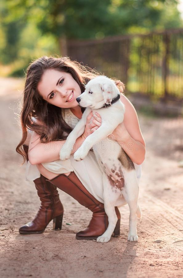 Stylish girl with a puppy in her hands royalty free stock photography